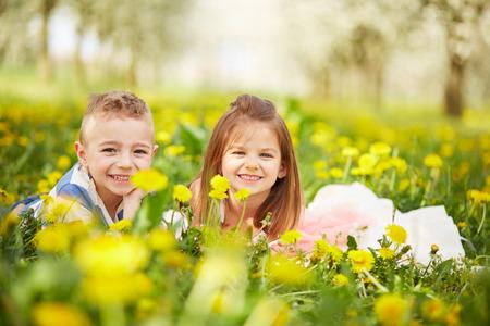 Chica tumbada con el niño en un huerto en flor