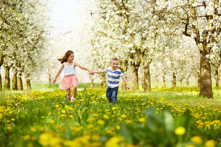 El muchacho va con la niña en un huerto en flor