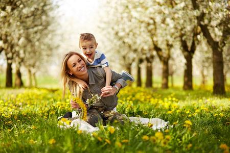 mamma figlio: Madre giocando con suo figlio in un frutteto in fiore
