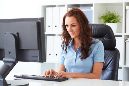mujeres trabajando: Mujer de negocios por escrito en un ordenador en la oficina