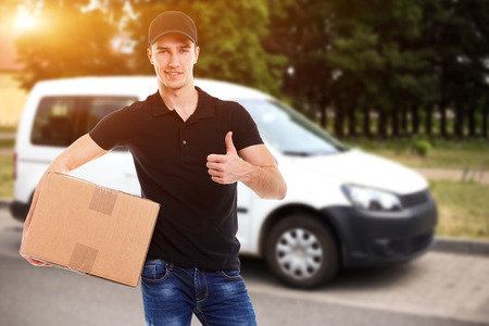 removal van: Smiling delivery man holding a cardboard box in sunlight