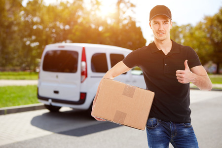 company: Smiling delivery man holding a cardboard box in sunlight