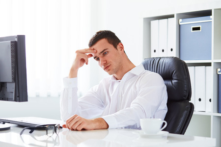 sitting at desk: Young business man under stress in the office