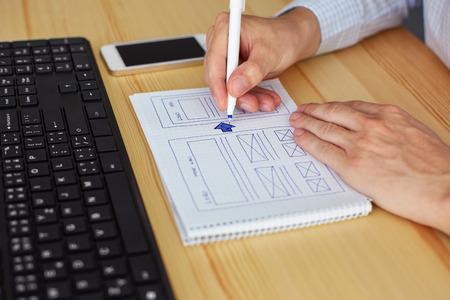 Hombre dibujando en el diseño de papel nuevo sitio web Foto de archivo