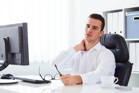 persona sentada: Hombre de negocios joven tiene dolor del cuello uterino en el trabajo