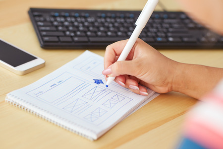Woman sketching on paper design new website Stockfoto