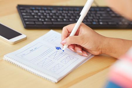 website design: Woman sketching on paper design new website Stock Photo