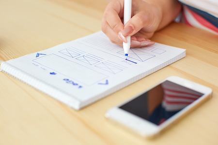 Diseñador gráfico bosquejar diseño web detrás del escritorio Foto de archivo