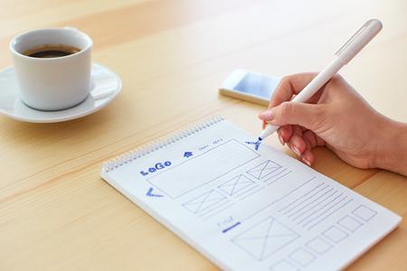 Grafisch ontwerper schetsen webdesign achter de balie Stockfoto