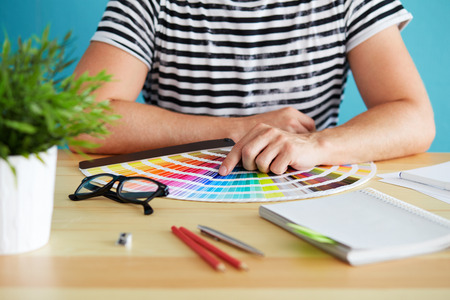 choosing: Graphic designer choosing a color from the sampler Stock Photo