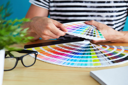 Graphic designer choosing a color from the palette Foto de archivo