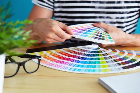 Graphic designer choosing a color from the palette Archivio Fotografico