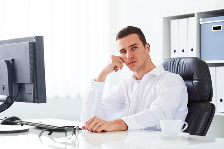 siting: Young handsome business man working in the office Stock Photo