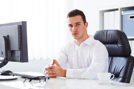 folded hands: Young businessman sitting in an office with hands folded