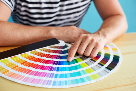 select: Graphic designer choosing a color from the sampler Stock Photo