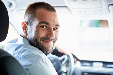 ハンサムな男は車に座って、振り返ってみると 写真素材