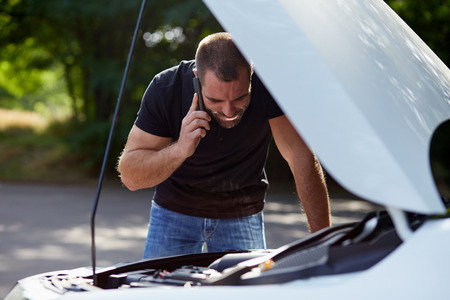 car trouble: Young man with a broken car calling for assistance Stock Photo
