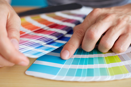 Graphic designer choosing a color from the palette Stockfoto