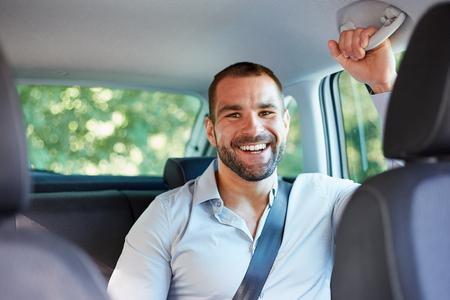 Jonge vrolijke zakenman zitten in een auto Stockfoto