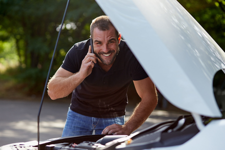 Lachende man belt iemand om hulp met zijn gebroken auto