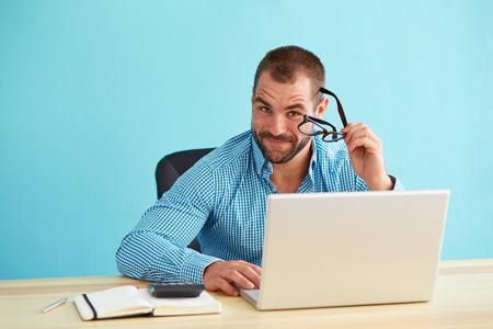 コンピューター上のモダンなオフィスで働く青年実業家