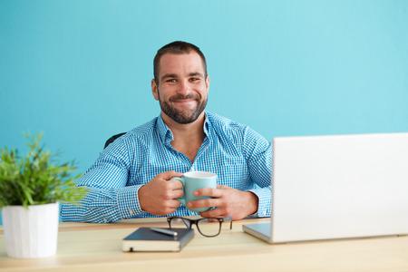 sonriente: Hombre joven en la oficina que sostiene una taza Foto de archivo