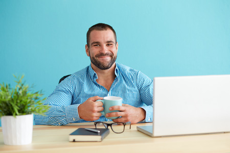 smiling: Young man in office holding a mug