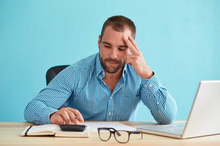 Homem de negócios pensativo calcula impostos na mesa no escritório Imagens