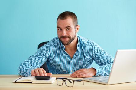 웃는 사업가 사무실에서 책상에서 세금을 계산합니다.