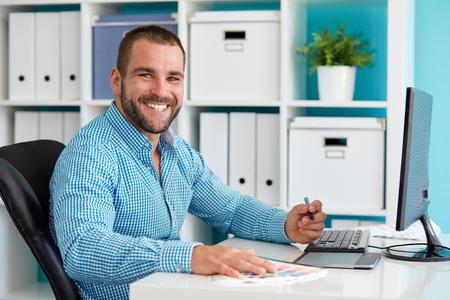 Diseñador gráfico feliz que trabaja en la tablilla digital Foto de archivo - 44500417