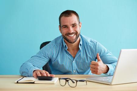 calculadora: Hombre de negocios sonriente calcula los impuestos y gesticula los pulgares para arriba