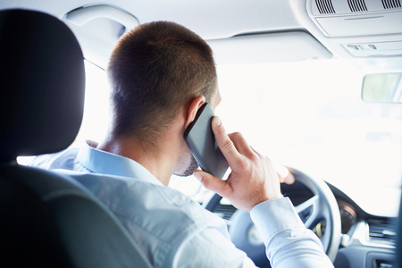 cellphones: Young businessman sitting in car and call Stock Photo