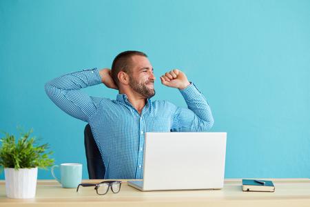 jovenes felices: Hombre que trabaja en el escritorio en la oficina estirar su espalda en el escritorio Foto de archivo