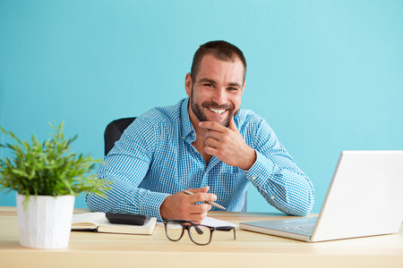 office manager: Happy businessman working with documents and laptop