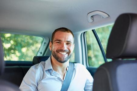 Hombre de negocios sonriente joven que se sienta en un coche