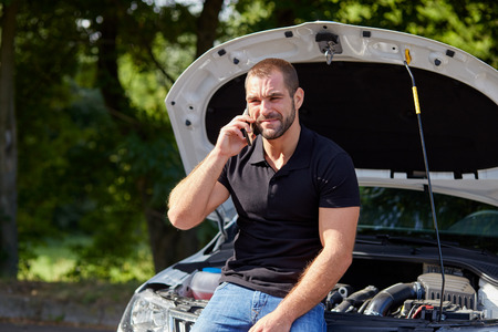Angry man sitting on a broken car calling for assistance