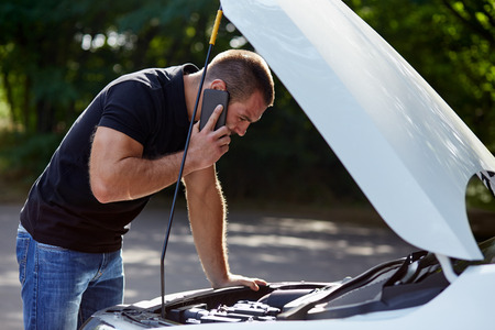 broken telephone: Man calling someone for help with his broken car