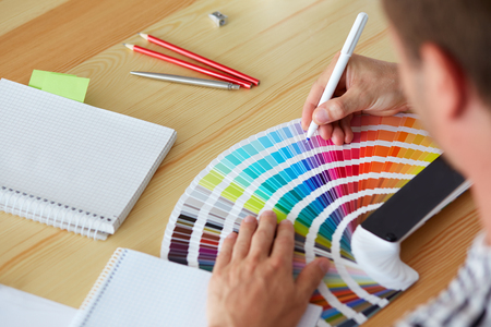 graphic designers: Graphic designer choosing a color from the sampler Stock Photo