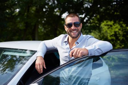 beau mec: Heureux l'homme debout et se penchant sur la porte de la voiture