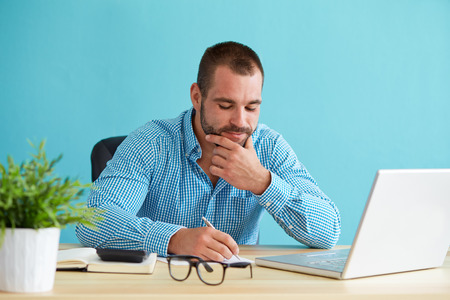 office man: Young businessman working with documents and laptop Stock Photo