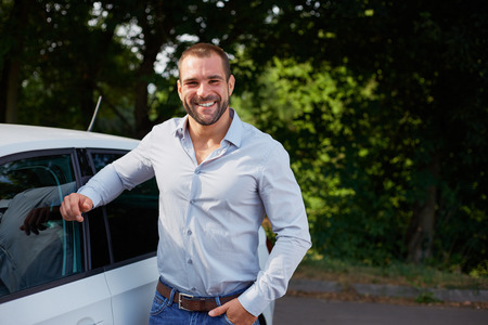 happy customer: Handsome man standing leaning on a car Stock Photo
