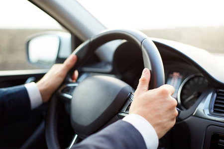 Male hands holding the steering wheel while driving