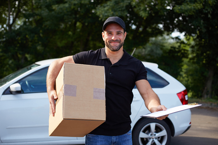 removal van: Smiling delivery man holding a paper box and folder