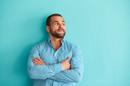 leaning against: Handsome man leaning against a turquoise wall