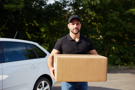Young delivery man holding a paper box Foto de archivo