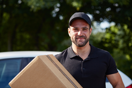 delivery box: Smiling delivery man holding a paper box Stock Photo
