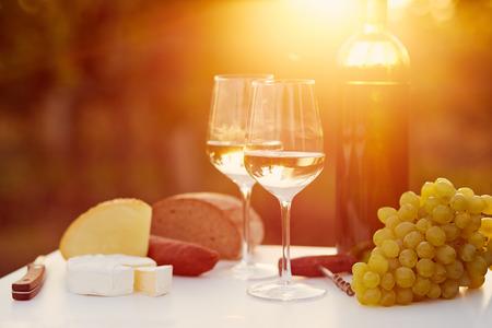 pan y vino: Dos vasos de vino blanco con la comida al atardecer, tonificado