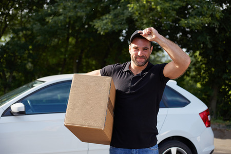 removal van: Smiling delivery man holding a paper box Stock Photo