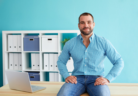 males: Young businessman sitting on desk in office