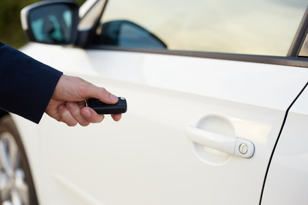 unlocking: Mens hand with key unlocking car door Stock Photo
